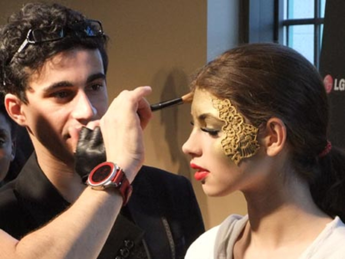 Eddie Malter applies makeup on model for Gaudet at LGFW fall 2010
