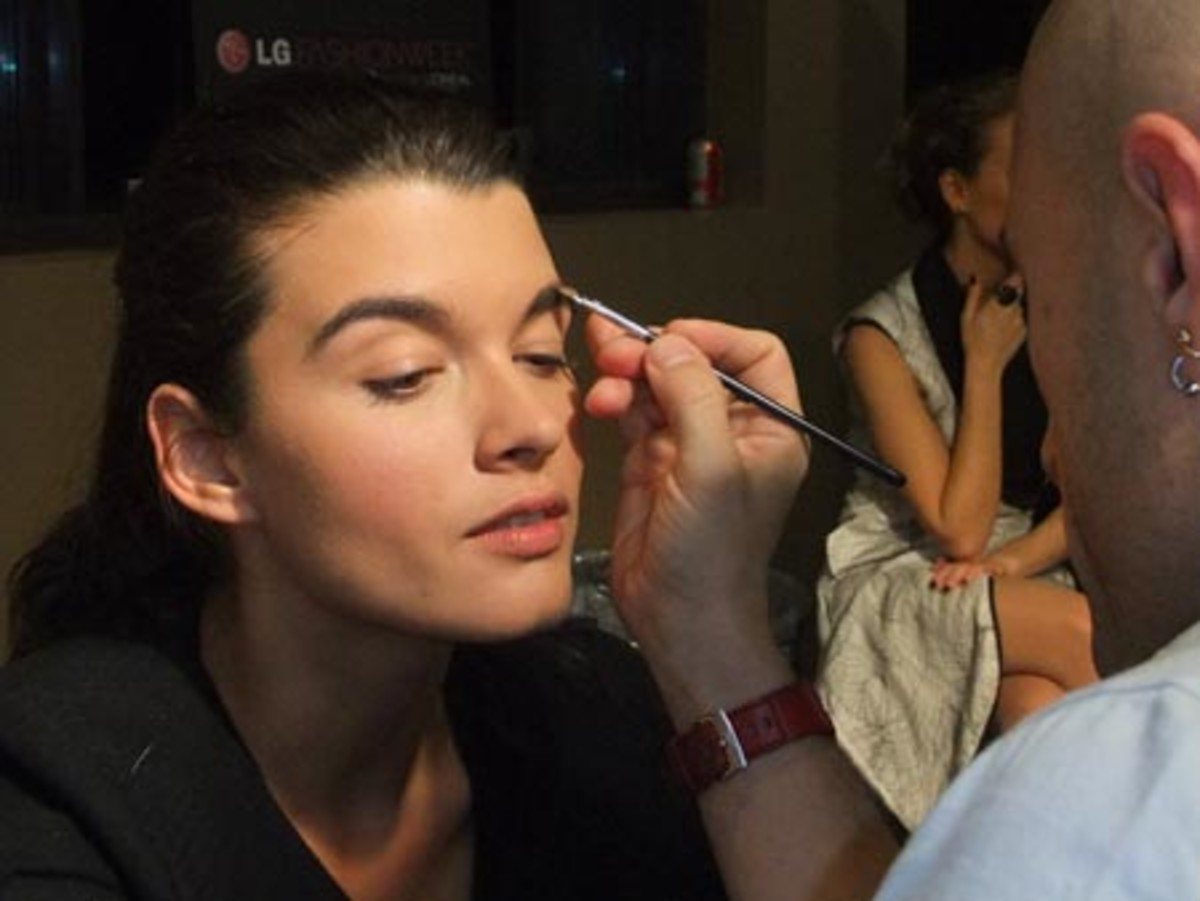 Crystal Renn w makeup artist Eddie Malter bkstg LG Fashion Week Fall 2010_photo by Janine Falcon