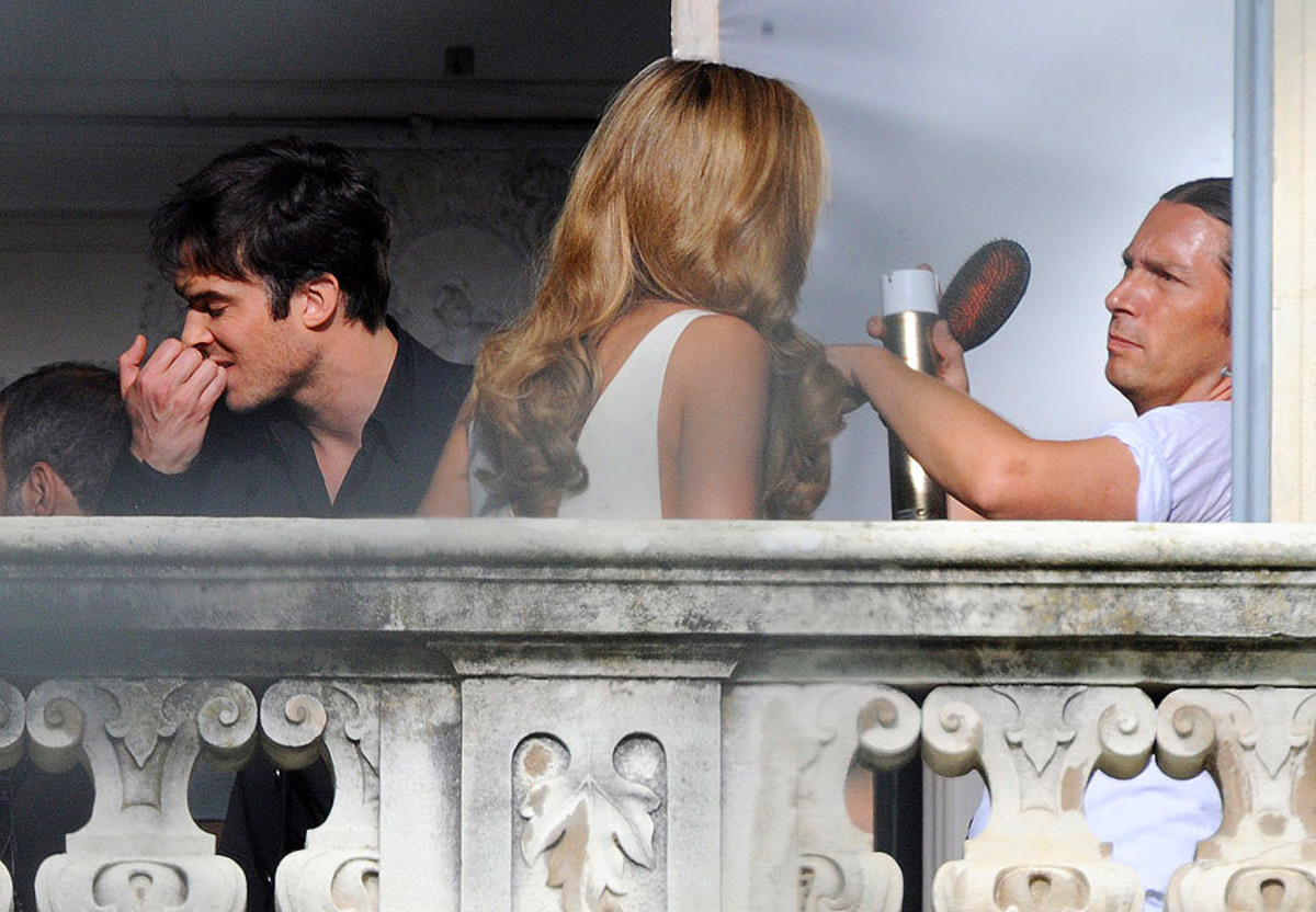 Ian Somerhalder bites his cuticles while hairstylist Maxime Mace uses Elnett hairspray on Ana Beatriz Barros
