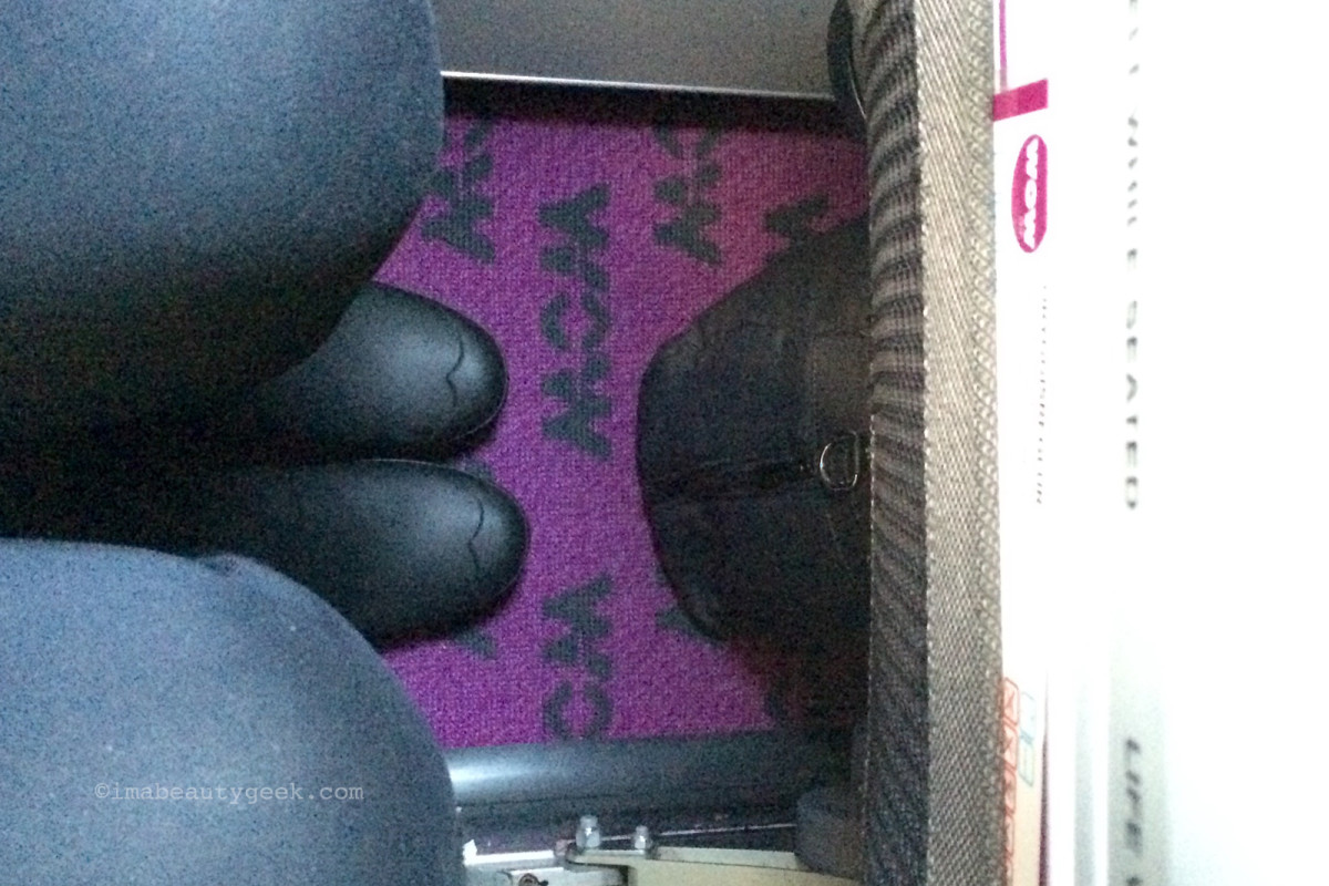 I'm sitting straight up in a Wow Air seat 4A, marvelling at the leg room as well as the magenta carpet.